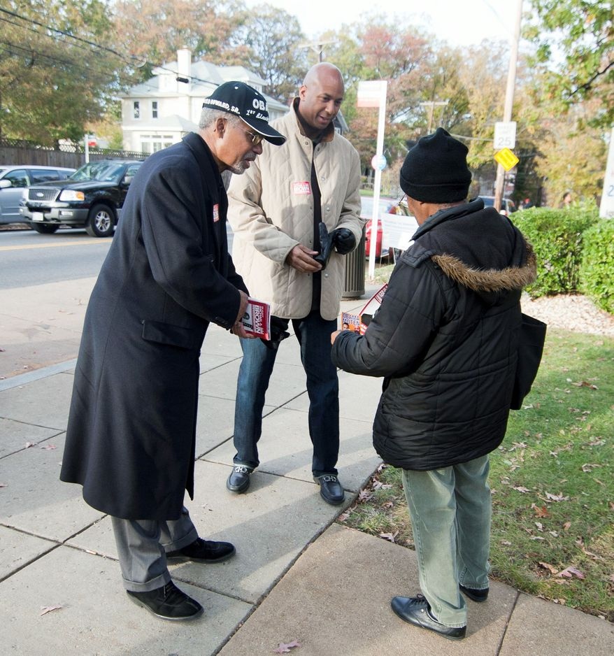 At large D.C. Council Member, Michael Brown, middle, greets voters outside of precinct 110 polling site in Washington, D.C., to cast their vote, Tuesday, Nov. 6, 2012 (Craig Bisacre/The Washington Times)