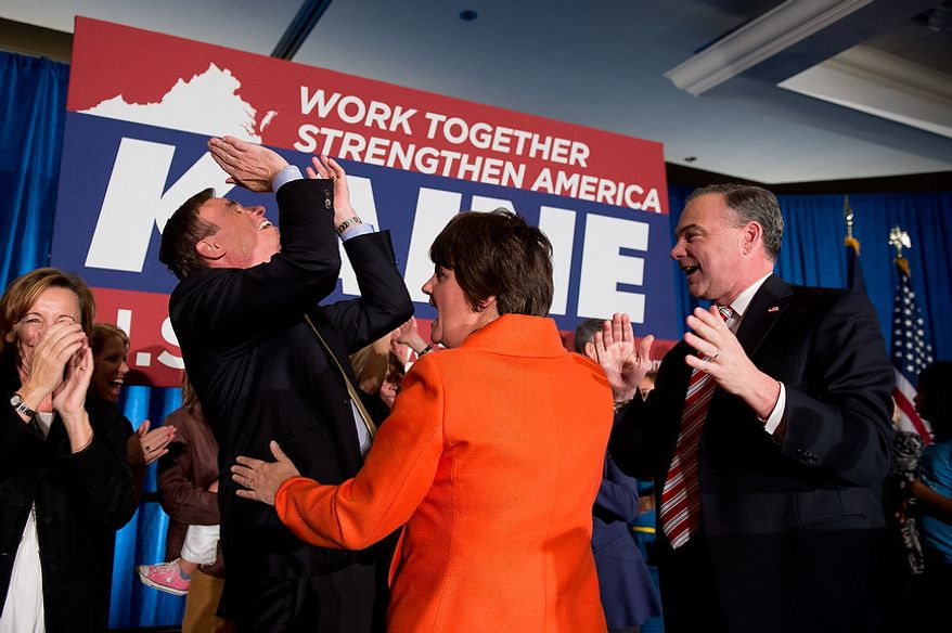 Sen. Mark Warner (D-Va.), left, Tim Kaine (D), right, and his wife Anne Holton, center, as they get word that President Barack Obama wins reelection during Kaine's victory speech after winning the Virginia election for U.S. Senate at his election night party at the Richmond Marriott, Richmond, Va., Tuesday, November 6, 2012. (Andrew Harnik/The Washington Times)
