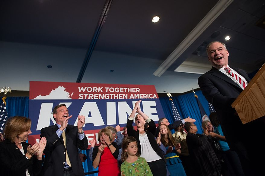 Sen. Mark Warner (D-Va.), second from left, cheers on Tim Kaine (D) as he delivers his victory speech after winning the Virginia election for U.S. Senate at his election night party at the Richmond Marriott, Richmond, Va., Tuesday, November 6, 2012. (Andrew Harnik/The Washington Times)