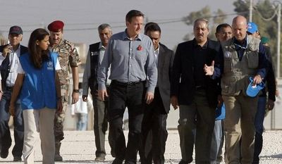 British Prime Minister David Cameron (front row center) walks with Jordanian Foreign Minister Nasser Judeh (second from right) and Andrew Harper (right), U.N. High Commissioner for Refugees (UNHCR) representative to Jordan, during his visit to the Zaatari refugee camp in Mafraq, Jordan, on Wednesday, Nov. 7, 2012. (AP Photo)