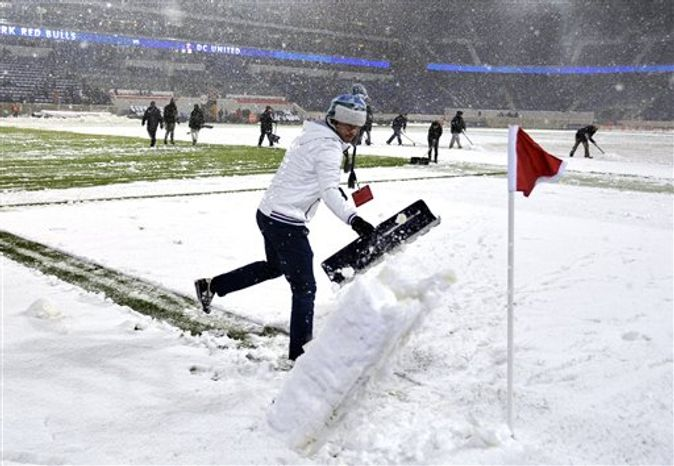 Workers attempt to clear the snow from the field before the New York Red Bulls' MLS Eastern Conference semifinal playoff match against D.C. United was postponed, Wednesday, Nov. 7, 2012, in Harrison, N.J. (AP Photo/Bill Kostroun)