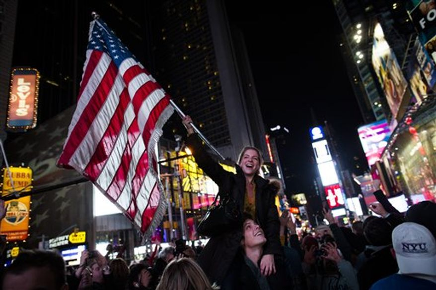 Megan Snedden, 26, of California, waves the American flag in Times Square to celebrate media outlets predicting President Barack Obama's reelection, Tuesday, Nov. 6, 2012, in New York. After a year of campaigning, polls have begun to close after Americans across the United States headed to the polls to decide the winner of the tight presidential race between President Barack Obama and former Massachusetts Governor Mitt Romney. (AP Photo/ John Minchillo)