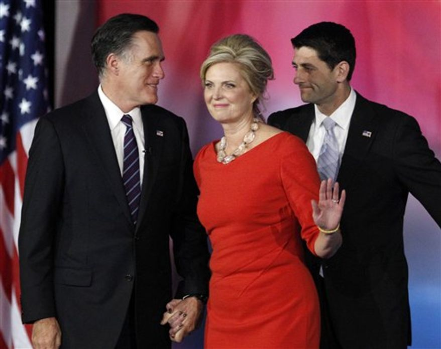 Republican presidential candidate and former Massachusetts Gov. Mitt Romney, left, wife Ann Romney, center, and Republican vice presidential candidate, Rep. Paul Ryan, R-Wis., stand on stage after Romney conceded the race during his election night rally, Wednesday, Nov. 7, 2012, in Boston. (AP Photo/Stephan Savoia)