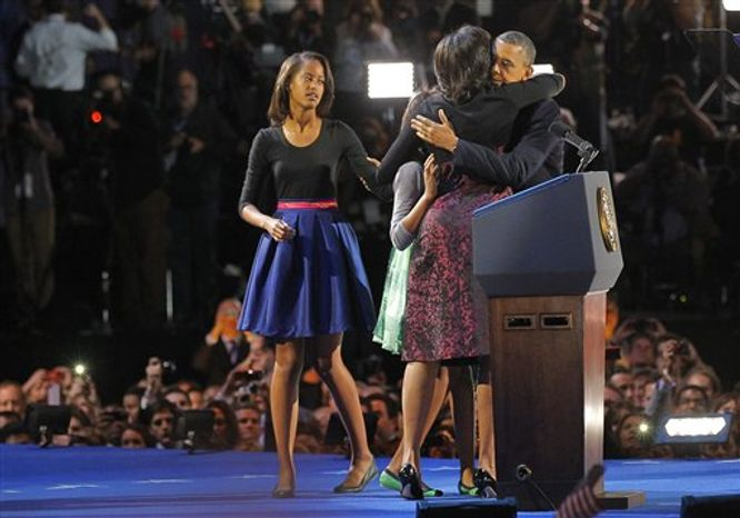 President Barack Obama hugs his wife Michelle and daughter Sasha as daughter Malia, left, looks on before speaking at his election night party, Wednesday, Nov. 7, 2012, in Chicago. President Obama defeated Republican challenger former Massachusetts Gov. Mitt Romney.  (AP Photo/Jerome Delay)