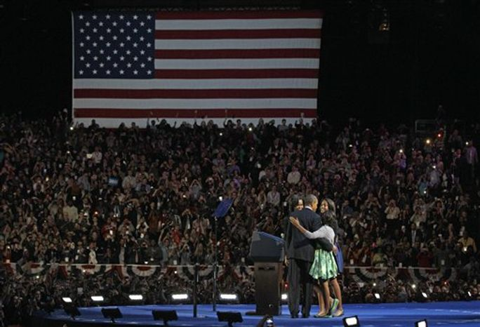 President Barack Obama walks out of the stage with his wife Michelle and daughters Sasha and Malia at his election night party Wednesday, Nov. 7, 2012, in Chicago. President Obama defeated Republican challenger former Massachusetts Gov. Mitt Romney.  (AP Photo/M. Spencer Green)
