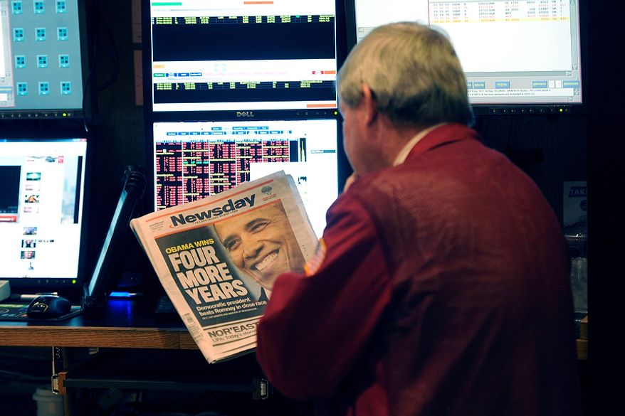 """A trader on the floor of the New York Stock Exchange looks at the front page of a newspaper the day after Pres. Barack Obama was re-elected, Wednesday, Nov. 7, 2012 in New York. With President Barack Obama elected to another term, U.S. investors dumped stocks Wednesday and turned their focus to a world of problems, including a """"fiscal cliff"""" of tax increases and spending cuts at home and a deepening recession in Europe. (AP Photo/Henny Ray Abrams)"""