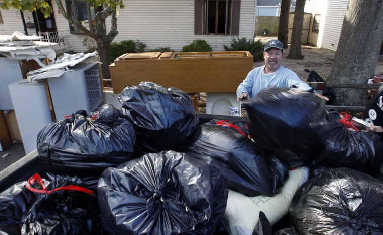 Bill Klipp of Florida works on cleaning out his father's flood-damaged home on Tuesday, Nov. 6, 2012, in Brick, N.J. The city is ordering mandatory evacuations in advance of an approaching nor'easter and in the wake of superstorm Sandy. (AP Photo/Mel Evans)