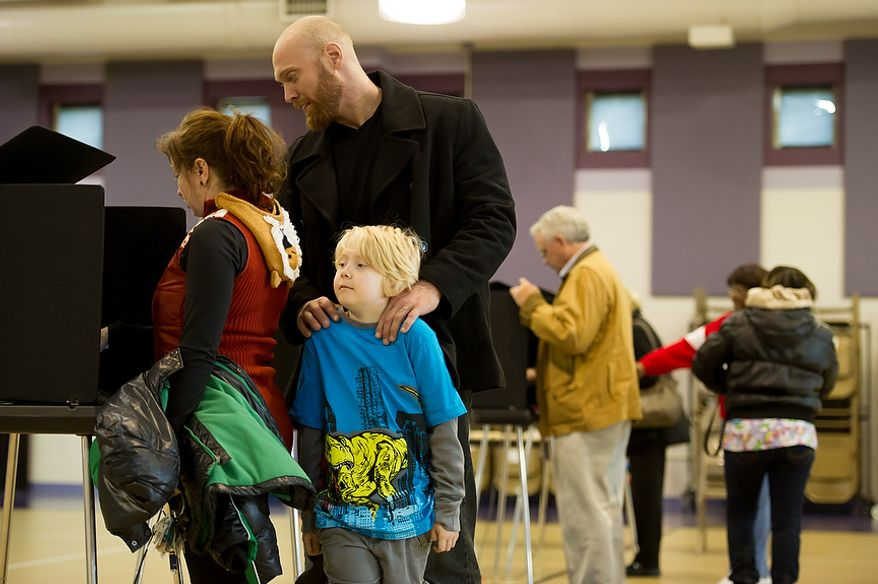 Rob Weaver and his son Ben Magnvs [cq], 7, waits for Jessica Weaver as she finishes voting at Linwood Holton Elementary School on election day morning, Richmond, Va., Tuesday, November 6, 2012. (Andrew Harnik/The Washington Times)
