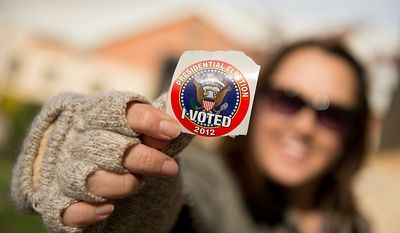 """Ina Moses of Richmond, Va., shows off her """"I Voted"""" sticker as she finishes voting at Linwood Holton Elementary School on election day morning, Richmond, Va., Tuesday, November 6, 2012. (Andrew Harnik/The Washington Times)"""