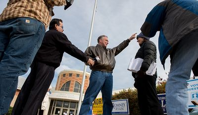 Democratic candidate for Senate Tim Kaine, center, points in the direction of his house as he chats with voter advocate Cecily Baskir of Chevy Chase, Md., second from right, outside the polling entrance at Linwood Holton Elementary School on election day morning, Richmond, Va., Tuesday, November 6, 2012. (Andrew Harnik/The Washington Times)