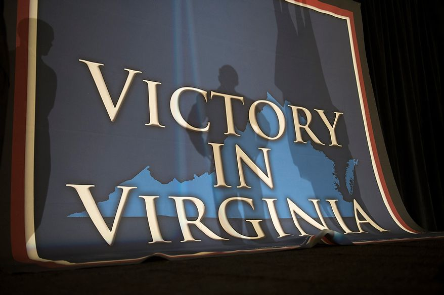Workers raise and adjust the backdrop banner on stage as crews prepare the ballroom at Republican U.S. Senate candidate and former Virginia Governor George Allen's election night party event at the Omni Richmond Hotel in Richmond, Va., Tuesday, Nov. 6, 2012. (Rod Lamkey Jr./The Washington Times)