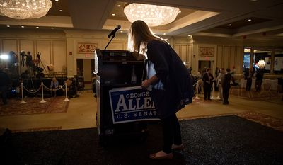 George Allen campaign finance director Gina Padrone collects campaign signs from the lectern after Republican U.S. Senate candidate and former Virginia Governor George Allen conceded the senate race to former Virginia Governor Tim Kaine, at the Omni Richmond Hotel in Richmond, Va., Tuesday, Nov. 6, 2012. (Rod Lamkey Jr./The Washington Times)