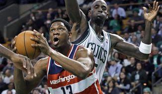 Washington Wizards forward Kevin Seraphin (13) drives to the basket past Boston Celtics forward Kevin Garnett during the first half of an NBA game in Boston on Wednesday, Nov. 7, 2012. (AP Photo/Elise Amendola)