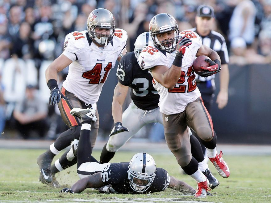 In this Nov. 4, 2012, file photo, Tampa Bay Buccaneers running back Doug Martin (22) runs for a 67-yard touchdown against the Oakland Raiders during the third quarter of an NFL football game in Oakland, Calif. Following a pair of dominating performances that not only thrust the rookie into the limelight, Martin has his team back on track. (AP Photo/Marcio Jose Sanchez, File)