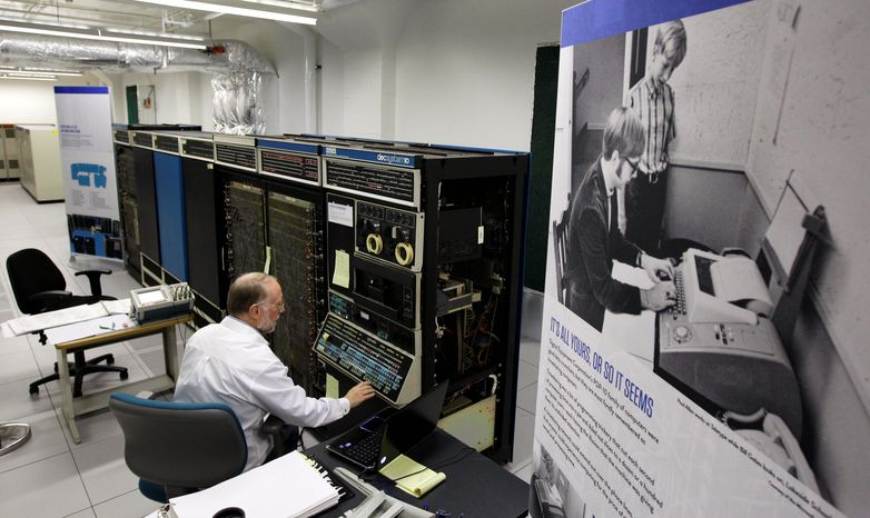In this photo taken Oct. 30, 2012, Bruce Sherry, a contract engineer at the Living Computer Museum in Seattle, manually programs a DEC PDP-10 computer from the early 1970s next to a photograph of Microsoft co-founders Paul Allen, seated, and Bill Gates, standing at Allen's left, working on a teletype machine. Allen has just opened the Living Computer Museum, which features working models of old computers. (AP Photo/Ted S. Warren)