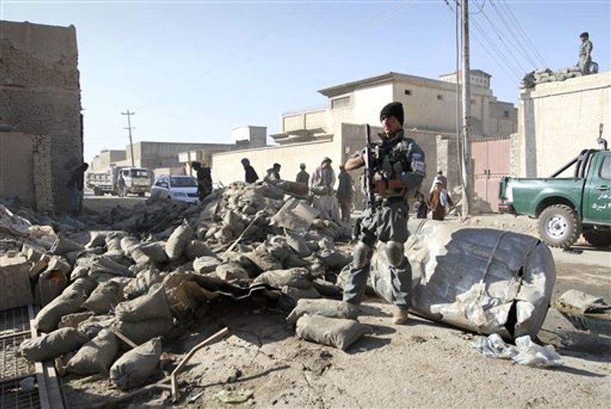 An Afghan policeman stands guard at the scene of a suicide attack in Kandahar, south of Kabul, Afghanistan, Thursday, Nov. 8, 2012. Ahmad Jawed Faisal, a provincial governor spokesman, says a suicide bomber killed several policemen and wounded others in the southern city of Kandahar on Thursday. (AP Photo/Allauddin Khan)