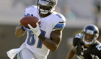 Detroit Lions wide receiver Calvin Johnson (81) catches a pass against Jacksonville Jaguars cornerback Derek Cox (21) during the second half of an NFL football game, Sunday, Nov. 4, 2012, in Jacksonville, Fla. Detroit beat Jacksonville 31-14. (AP Photo/Stephen Morton)