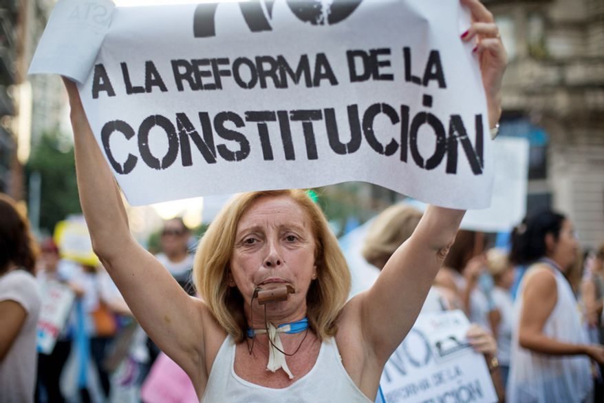 """A protester carries a sign that reads in Spanish """"No to constitutional reform"""" during anti-government demonstration in Buenos Aires, Argentina.  (AP Photo/Victor R. Caivano)"""