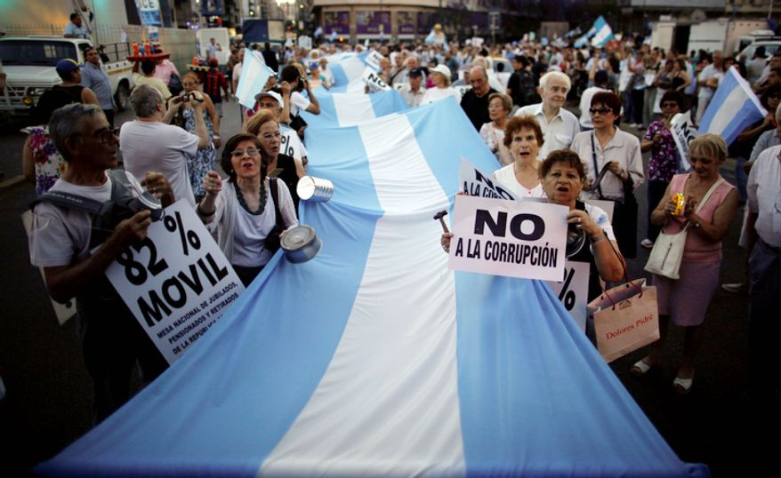 """People march with an Argentine flag during an anti-government demonstration, one carrying a sign that reads in Spanish """"No to corruption,"""" right, in Buenos Aires, Argentina. Thousands of people marched against rising inflation, crime, exchange controls and to express their fear to a constitutional reform that could open the way for a third consecutive reelection of Argentina's President Cristina Fernandez. (AP Photo/Natacha Pisarenko)"""