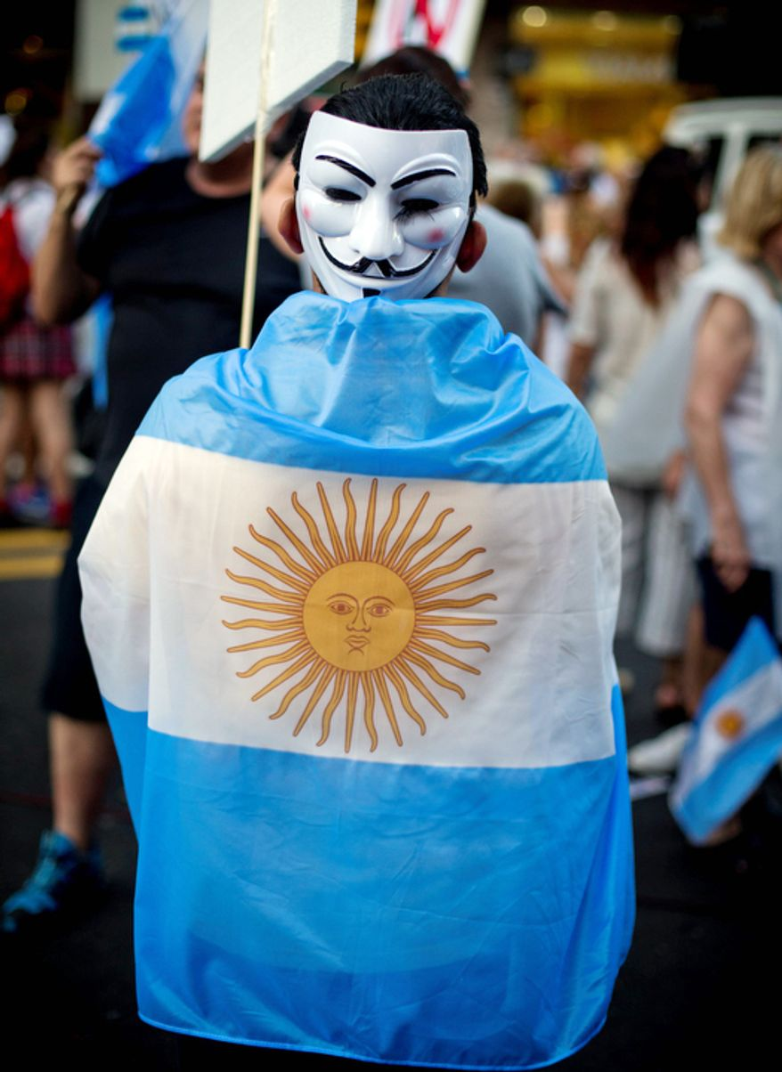 A protester wearing a mask on the back of his head and an Argentine flag marches during anti government demonstration in Buenos Aires, Argentina. (AP Photo/Victor R. Caivano)