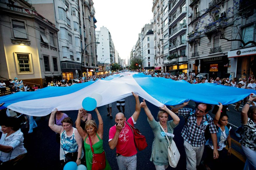 Protesters carry a large Argentine flag during an anti-government demonstration in Buenos Aires, Argentina.  (AP Photo/Victor R. Caivano)