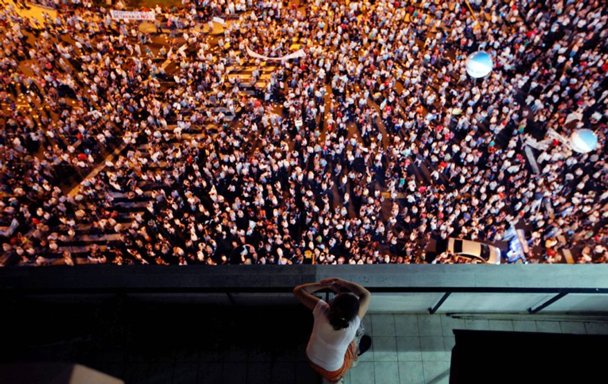 A woman watch from a balcony as protesters demonstrate during a march against Argentina's President Cristina Fernandez in Buenos Aires, Argentina, Thursday, Nov. 8, 2012. (AP Photo/Natacha Pisarenko)