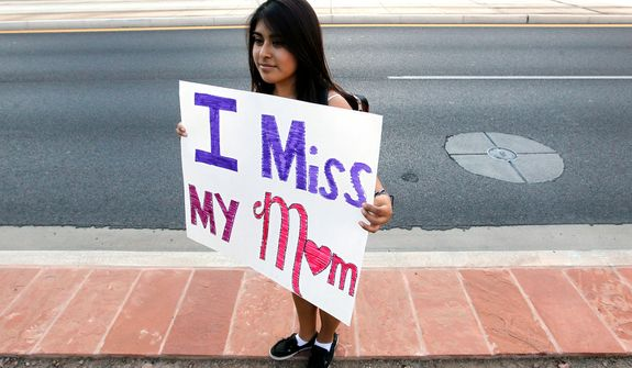 "**FILE** Cynthia Diaz, 17, quietly holds up a sign Sept. 19, 2012, dedicated to her mother as she joins dozens who rally in front of U.S. Immigration and Customs Enforcement building, a day after a portion of Arizona's immigration law took effect in Phoenix. Her mother was deported the previous year. Civil rights activists contend the state's law will lead to systematic racial profiling, as the protesters chanted ""No papers, no fear."" (Associated Press)"