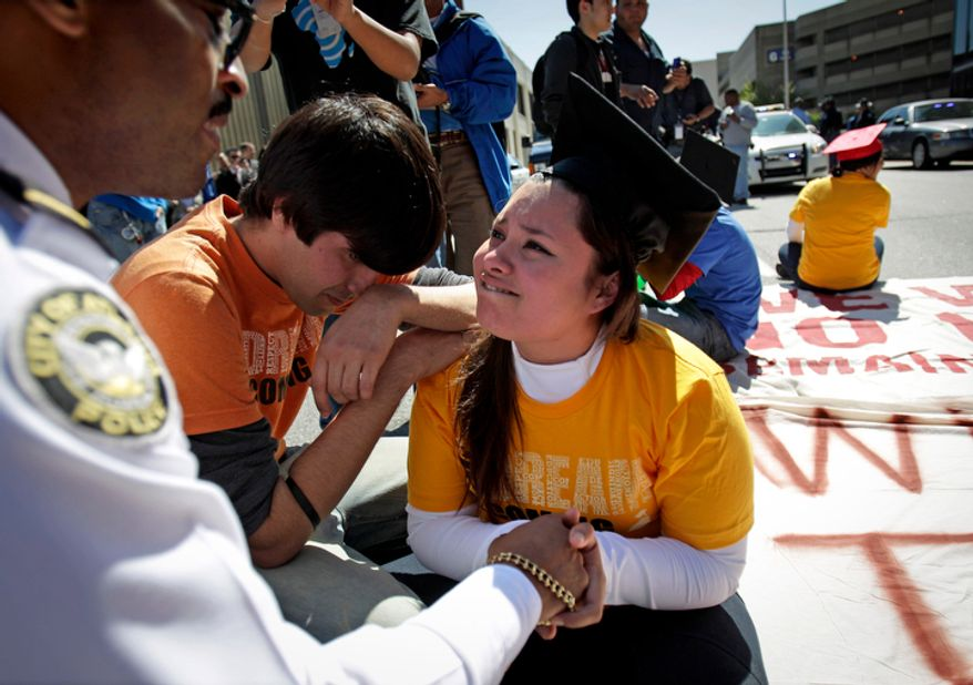 **FILE** Illegal immigrant Viridiana Martinez (right) is comforted April 5, 2011, by activist Mohammad Abdollahi as Maj. K.E. Williams (left) of the Atlanta Police Department warns her of arrest unless she moves during a protest for rights for higher education for illegal immigrants in Atlanta. (Associated Press)