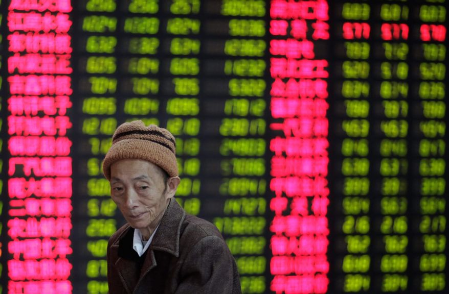An investor looks at the stock price monitor at a private securities company in Shanghai on Nov. 8, 2012. Asian stock markets tumbled after a ratings agency threatened to downgrade the U.S. if a solution to the so-called fiscal cliff isn't negotiated among lawmakers and newly re-elected President Obama. (Associated Press)