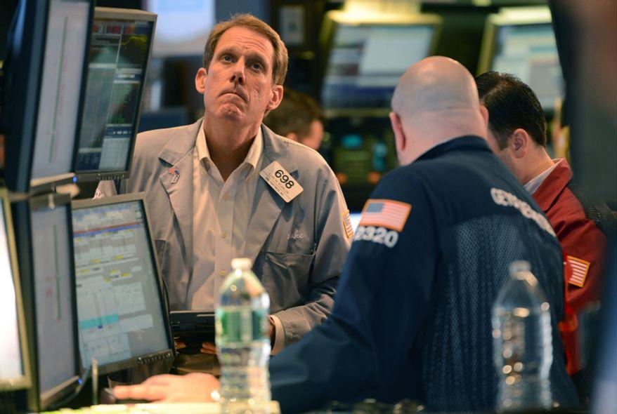 Luke Scanlon (left) of MND Partners Inc., works Nov. 7, 2012, on the floor of the New York Stock Exchange in New York. (Associated Press)