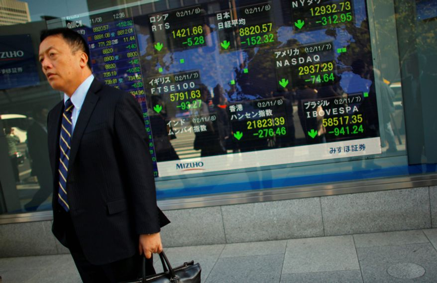 A man stands outside a securities firm in Tokyo on Nov. 8, 2012. Asian stock markets tumbled after a ratings agency threatened to downgrade the U.S. if a solution to the so-called fiscal cliff isn't negotiated among lawmakers and newly re-elected President Obama. (Associated Press)