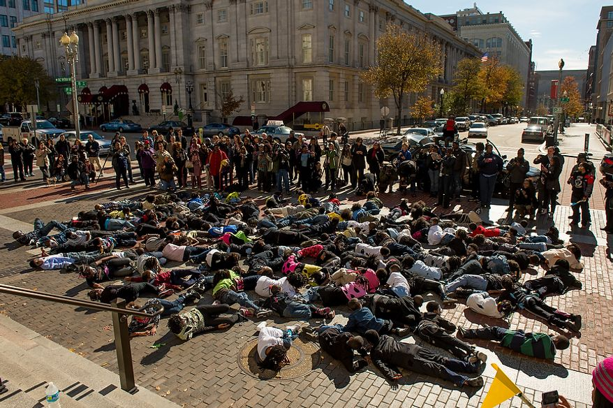 """Savoy Elementary School students lay on the ground to begin their flash mob dance performance to Michael Jackson's """"Thriller"""" in front of the National Portrait Gallery as a way to teach music theory, movement and the impact of the song on the music industry and the """"cultural fabric of our society,"""" Washington, D.C., Thursday, November 8, 2012. (Andrew Harnik/The Washington Times)"""