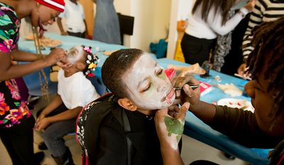 """Savoy Elementary School students Hope Brown, 7, second from left, and Deshean Dean, 9, center, get their makeup done by Rechelle Rice, left, and Otisi Okiyi Jr., right, both part time art program assistants before students perform a flash mob dance to Michael Jackson's """"Thriller"""" in front of the National Portrait Gallery as a way to teach music theory, movement and the impact of the song on the music industry and the """"cultural fabric of our society,"""" Washington, D.C., Thursday, November 8, 2012. (Andrew Harnik/The Washington Times)"""