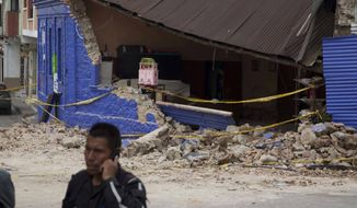 Yellow taped is draped in front of a home damaged in a magnitude 7.4 earthquake that struck in San Marcos, Guatemala, Wednesday, Nov. 7, 2012. (AP Photo/Moises Castillo)