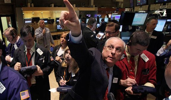 **FILE** Nicholas Briganti (center), governor of the New York Stock Exchange, works with traders on the floor of the Exchange on April 12, 2012. (Associated Press)
