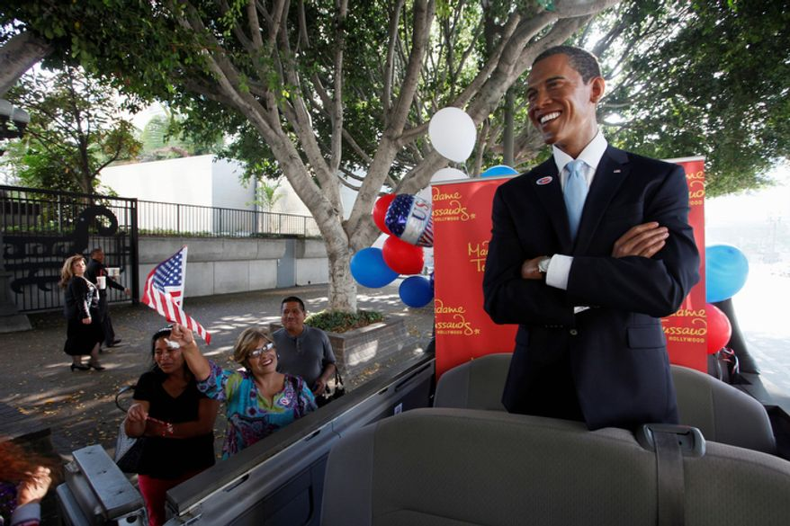 Pedestrians greet a wax figure of President Obama from Madame Tussaud's Hollywood museum outside City Hall in Los Angeles on Nov. 7, 2012. The Obama figure was touring parts of the city in honor of his Election Day victory the previous day. (Associated Press)