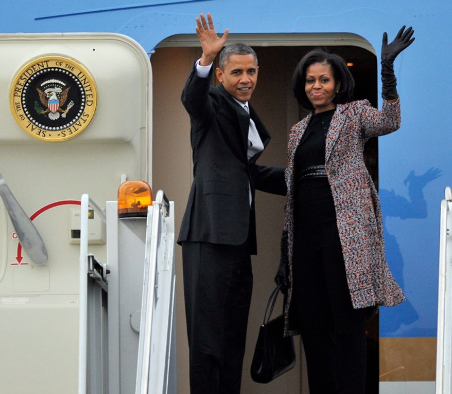 President Obama and first lady Michelle Obama wave while boarding Air Force One before leaving O'Hare International Airport in Chicago on Nov. 7, 2012. (Associated Press)