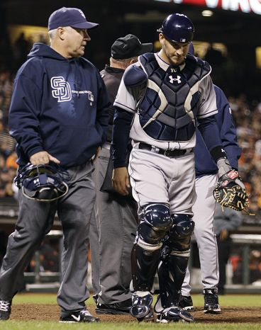 FILE - In this Sept. 21, 2012, file photo, San Diego Padres catcher Yasmani Grandal, right, leaves the field with an injury in the seventh inning of a baseball game against the San Francisco Giants in San Francisco. The commissioner's office announced Wednesday, Nov. 7, that Grandal has been suspended 50 games because of a positive test for testosterone. (AP Photo/Ben Margot, File)