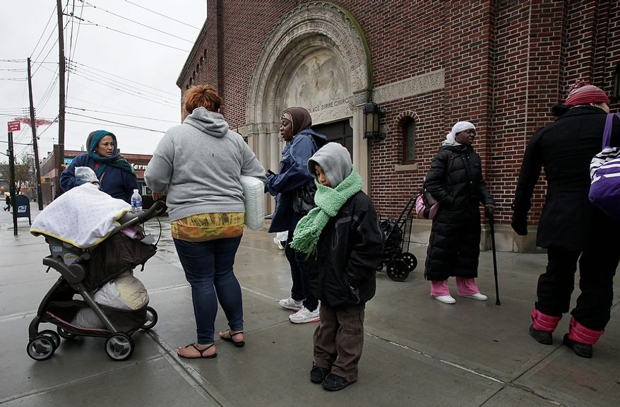 Axel Benitez, 7, his mother, Lucia Figueroa (second from left), and his baby sister, Jelannie (in stroller), evacuate from Coney Island in New York with the assistance of friends on Nov. 7, 2012 in New York, as a new storm approached the region on the heels of Superstorm Sandy. (Associated Press)