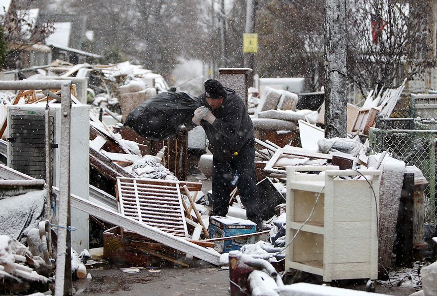 Jason Auer works in the snow cleaning a relatives house in the New Dorp section of Staten Island, New York, Wednesday, Nov. 7, 2012. (AP Photo/Seth Wenig)