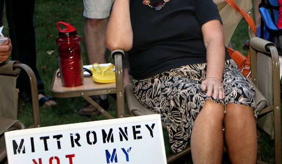**FILE** Ann Kalifrath listens Sept. 4, 2011, to Republican presidential candidate Mitt Romney speak at a Tea Party Express rally in Concord, N.H. (Associated Press)
