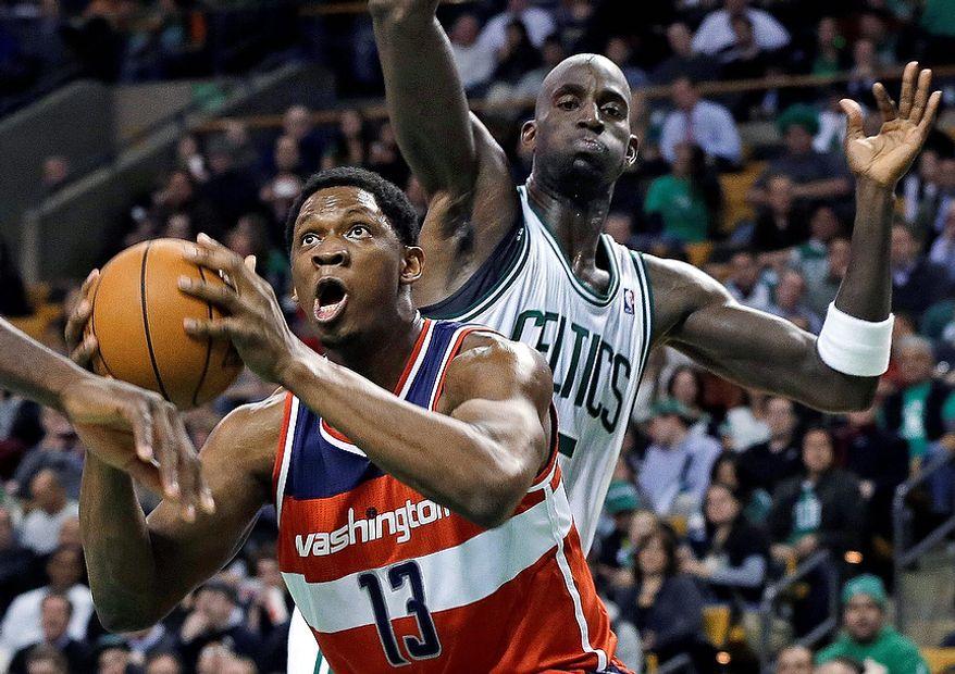 Washington Wizards forward Kevin Seraphin (13) drives to the basket past Boston Celtics forward Kevin Garnett during the first half of an NBA basketball game in Boston on Wednesday, Nov. 7, 2012. (AP Photo/Elise Amendola)