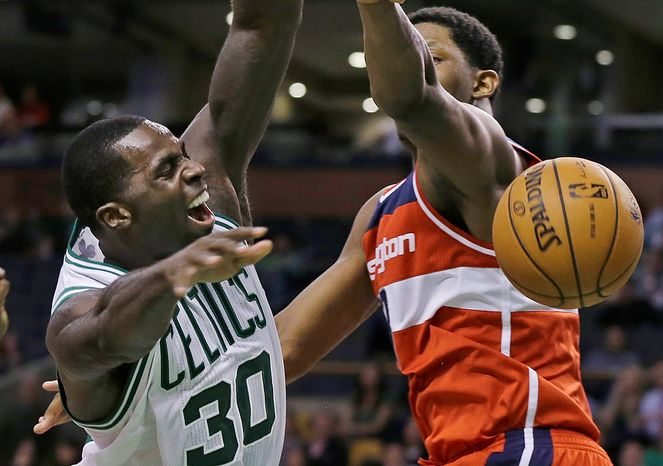 Boston Celtics forward Brandon Bass (30) is fouled by Washington Wizards forward Kevin Seraphin, right, as he goes to the basket during overtime in an NBA basketball game in Boston, Wednesday, Nov. 7, 2012. The Celtics won 100-94 in overtime. (AP Photo/Elise Amendola),