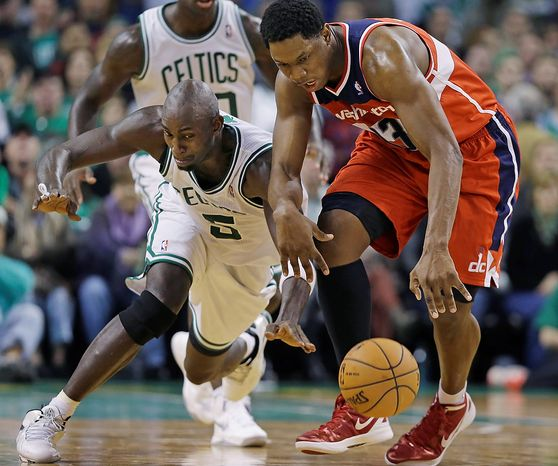 Boston Celtics forward Kevin Garnett (5) tries to steal the ball from Washington Wizards forward Kevin Seraphin, right, during the second half of an NBA basketball game in Boston, Wednesday, Nov. 7, 2012. The Celtics won 100-94 in overtime. (AP Photo/Elise Amendola)