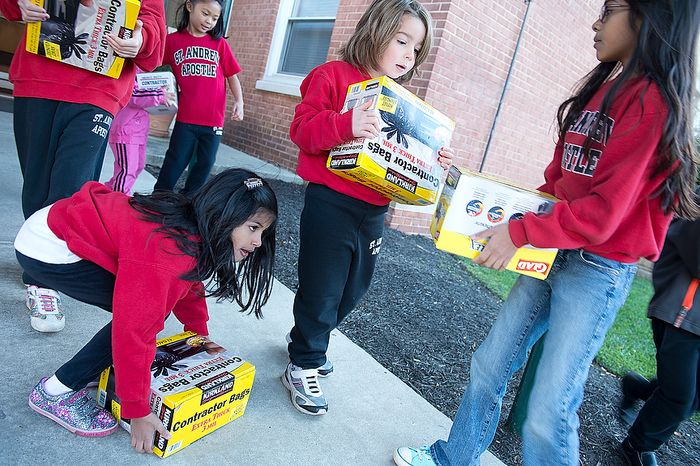 Sara Thomas (left), 7, picks up a dropped box of trash bags while Julia Luksic (center), 5, and Mira Thomas (right), 9, also carry trash bags to a big passenger van that is being loaded with donations to go to Superstorm Sandy victims in New Jersey on Nov. 9, 2012, at St. Andrew the Apostle Catholic Church in Silver Spring, Md. (Barbara L. Salisbury/The Washington Times)