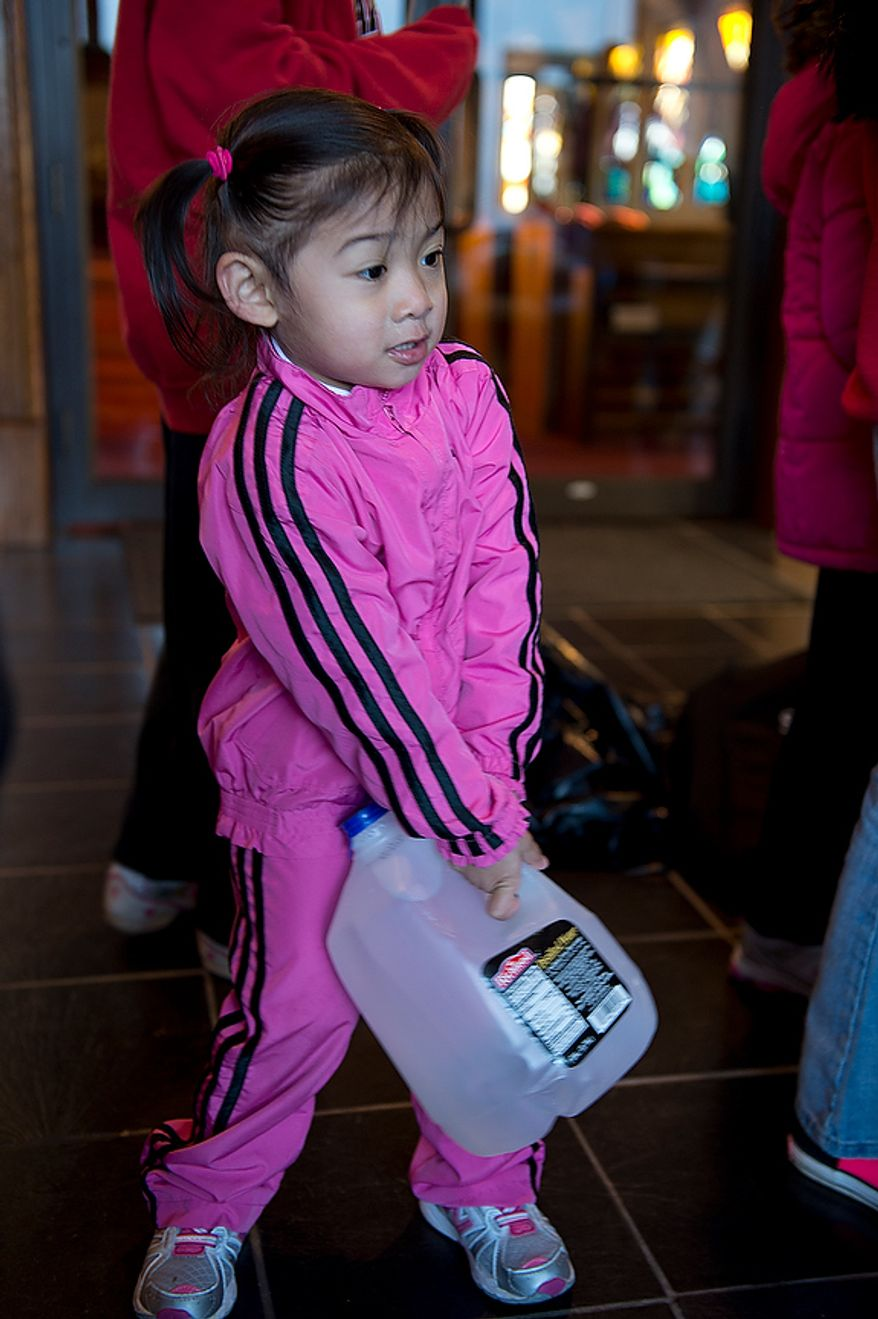Rory Sejismundo, 2, carries a bottle of water inside the front hallway of St. Andrew the Apostle Catholic Church in Silver Spring, Md. on Nov. 9, 2012. Water was among the donated supplies that will be sent from this church in a passenger van up to a church in New Jersey for victims of Superstorm Sandy. (Barbara L. Salisbury/The Washington Times)