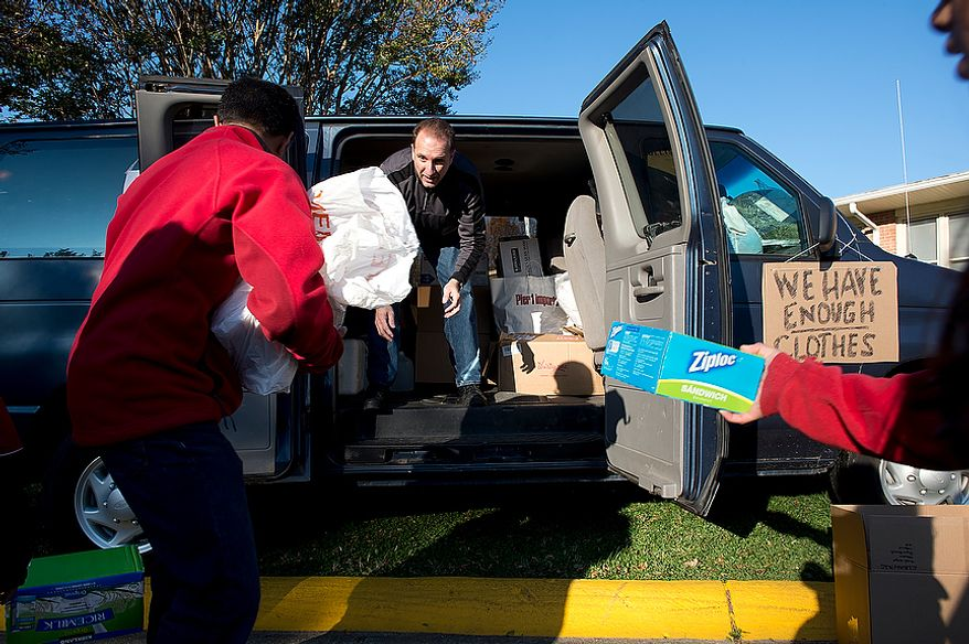 Mike Trigiani (center), a parishioner at St. Andrew the Apostle Catholic Church in Silver Spring, Md., loads donated items into a passenger van outside the church on Nov. 9, 2012. The van, which was filled with food, clothes, toiletries, cleaning supplies and baby products, will be driven to St. Benedict Church in Holmdel, N.J., where the supplies will be distributed to victims of Superstorm Sandy. (Barbara L. Salisbury/The Washington Times)