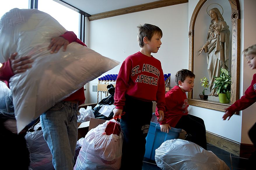 Children from St. Andrew the Apostle Catholic Church in Silver Spring, Md., including Joseph Luksic, 8, second from right, and Isabella Merino, 8, far right, wait inside their church with bags full of donated items to be taken to New Jersey for victims of Superstorm Sandy on Nov. 9, 2012. (Barbara L. Salisbury/The Washington Times)