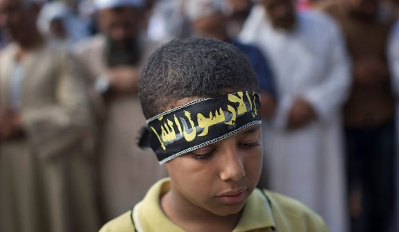 """An Egyptian Muslim child prays during a Nov. 9, 2012, rally in Tahrir Square in Cairo. Thousands of ultraconservative Muslims rallied in the Egyptian capital, demanding the country's new constitution be based on the rulings of Islamic law, or Shariah. (Associated Press) The boy's headband reads, in Arabic, """"anything but God's messenger."""" (Associated Press)"""