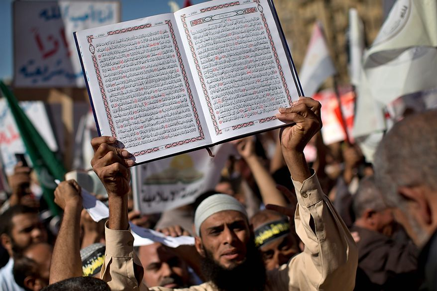 An Egyptian Muslim man holds the Quran, Islam's holy book, during a Nov. 9, 2012, rally in Tahrir Square in Cairo. Thousands of ultraconservative Muslims rallied in the Egyptian capital, demanding the country's new constitution be based on the rulings of Islamic law, or Shariah. (Associated Press)